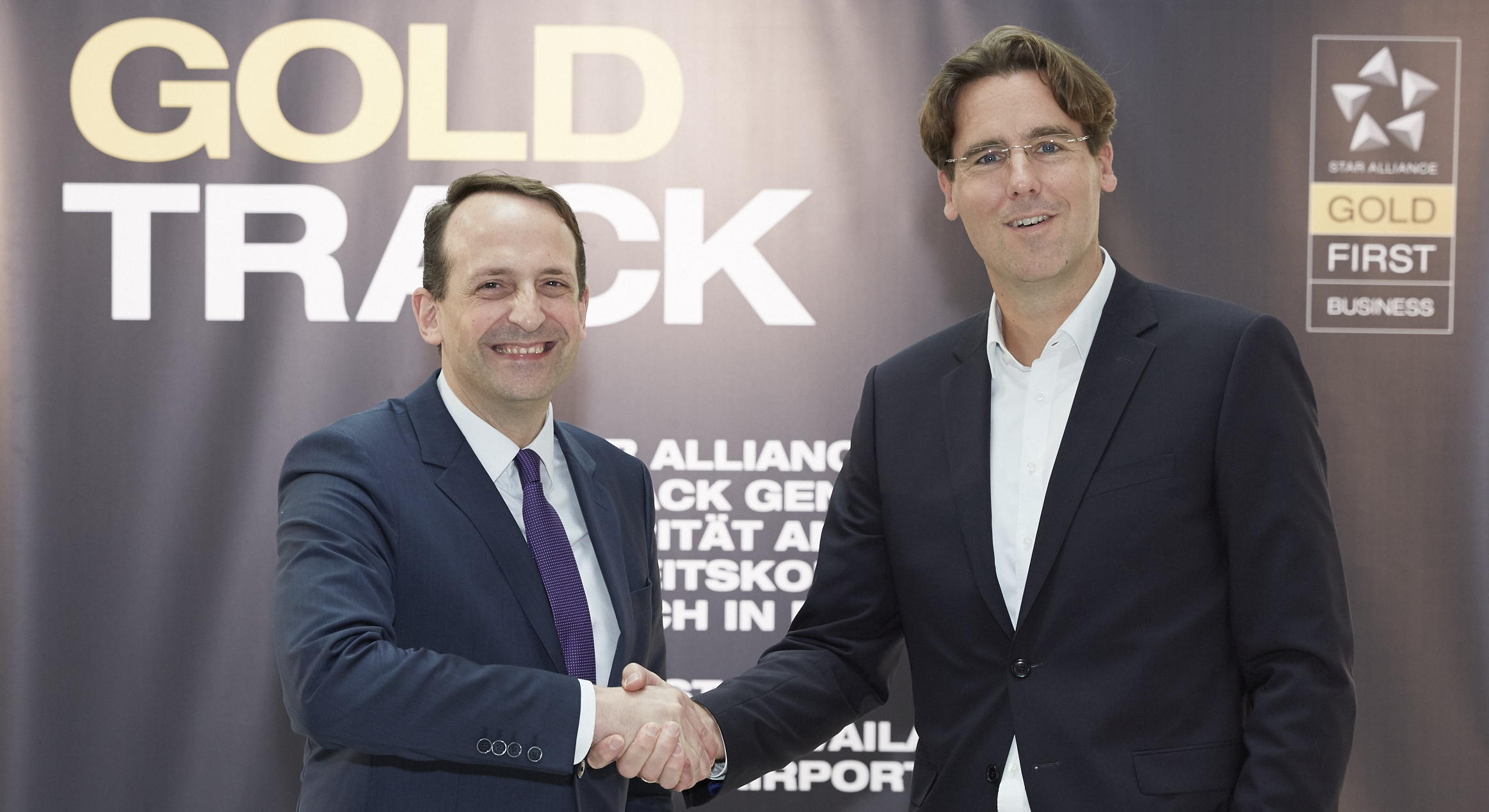 Senior Executive Vice President at Fraport AG for Airside & Terminal Management, Corporate Safety & Security Pierre Dominique Prümm (left) shakes hands with Lufthansa's Björn Becker, Senior Director Product Management Ground & Digital Services after Star Alliance Gold Track branding is installed in Frankfurt airport